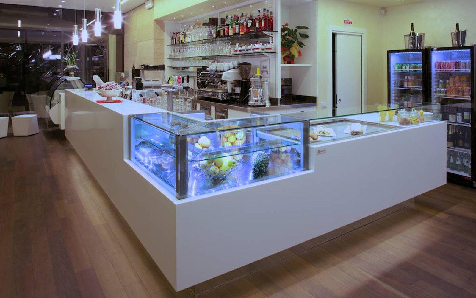 interno di un bar e vista del bancone con una vetrina e della frutta