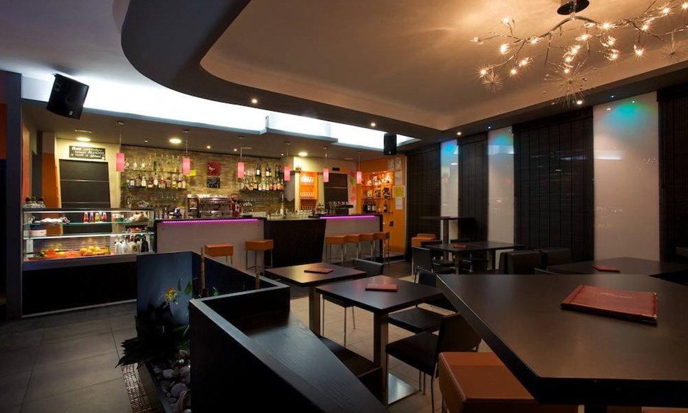 interno di un bar con tavoli neri, sedie e sgabelli arancioni