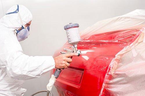 Operaio mentre vernicia una macchina