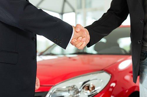 La stretta di mano di due professionisti con sfondo di una macchina rossa a Torino - carrozziere di fiducia