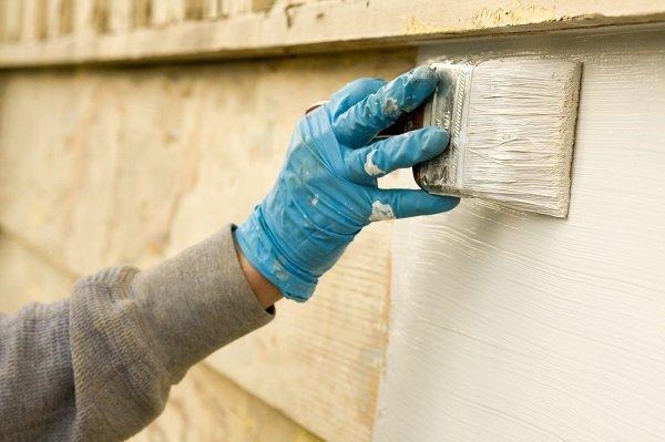 mano che tinteggia parete