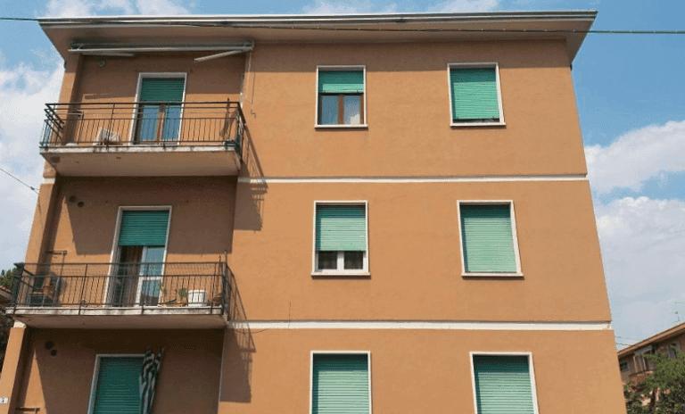 vista facciata di una casa con finestre verdi