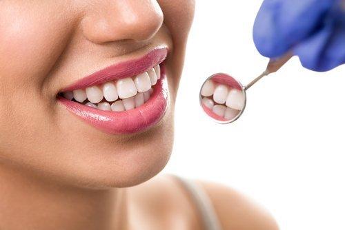 primo piano di paziente che si guarda i denti nello specchietto