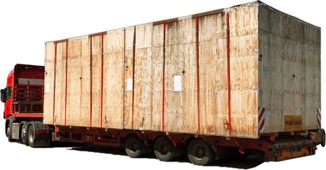 A low loader carrying a massive crate