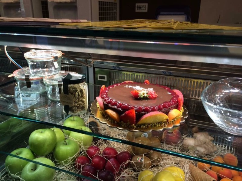 una vetrina con una torta alla frutta e altra frutta