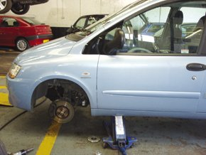 a blue car on a jack and the wheel taken off.