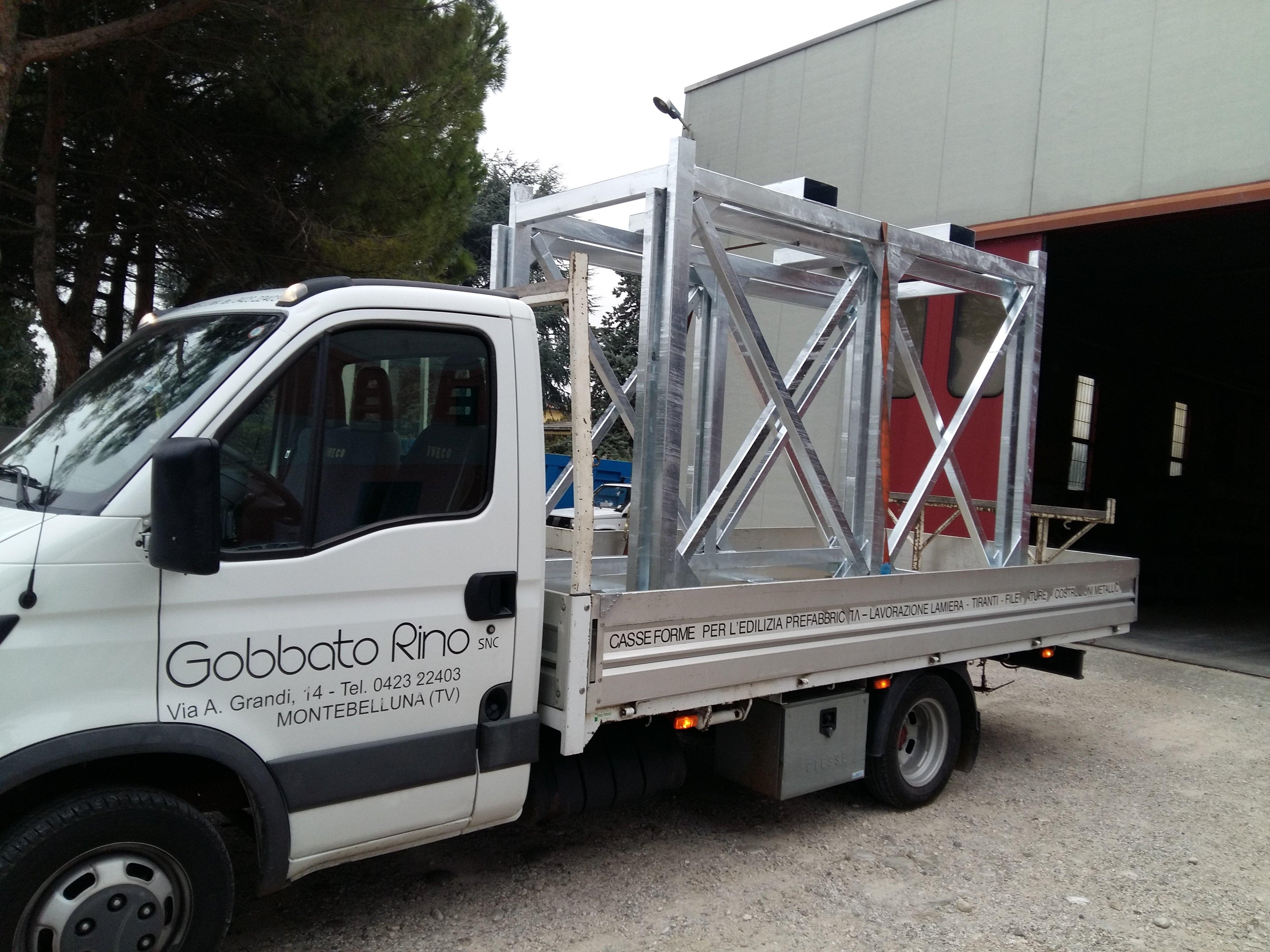 furgoncino bianco che trasporta una struttura metallica