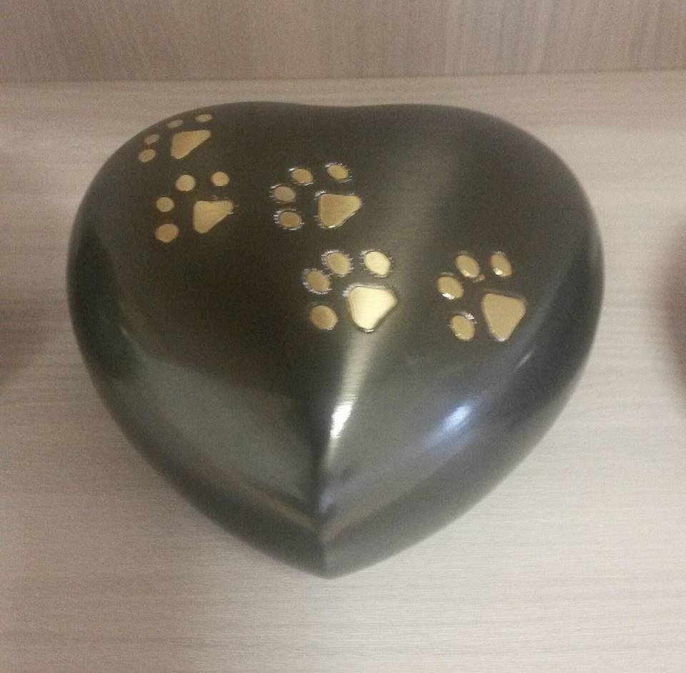 un'urna a forma di un cuore con sopra delle impronte delle zampe