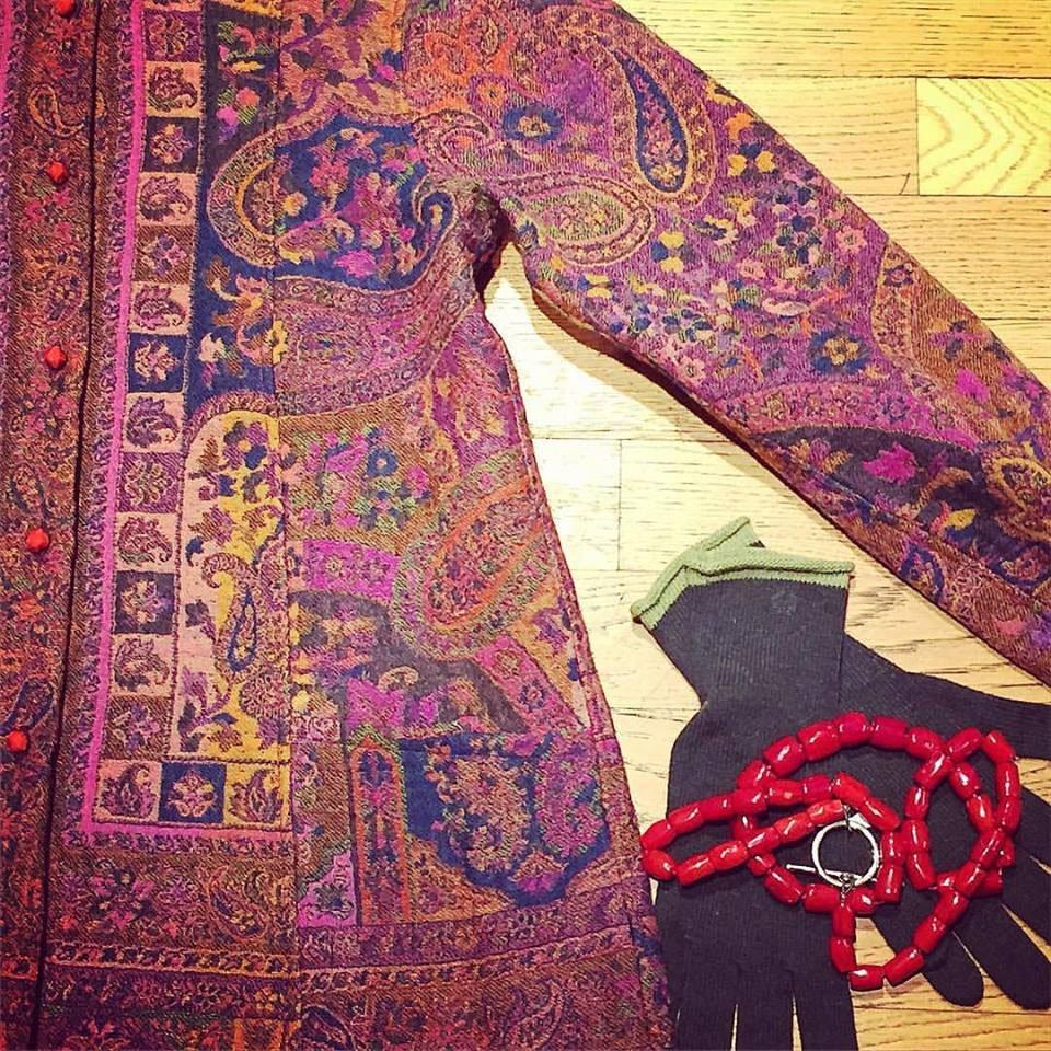 giacca di color rosa a fiori e accanto dei guanti neri e una collana rossa