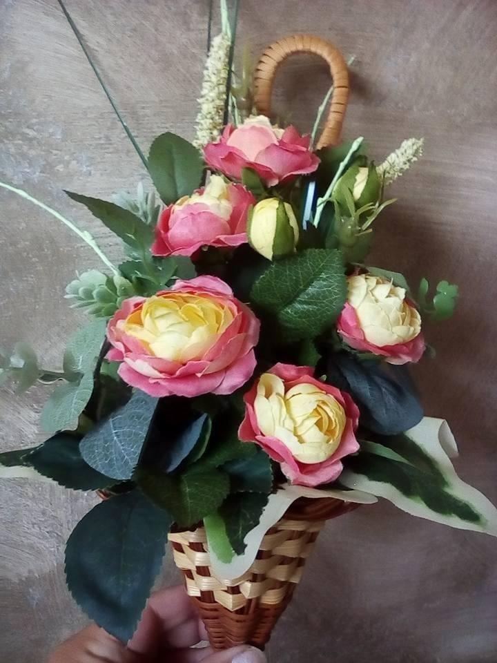 vaso di fiori in un mano con fiori rose e gialli