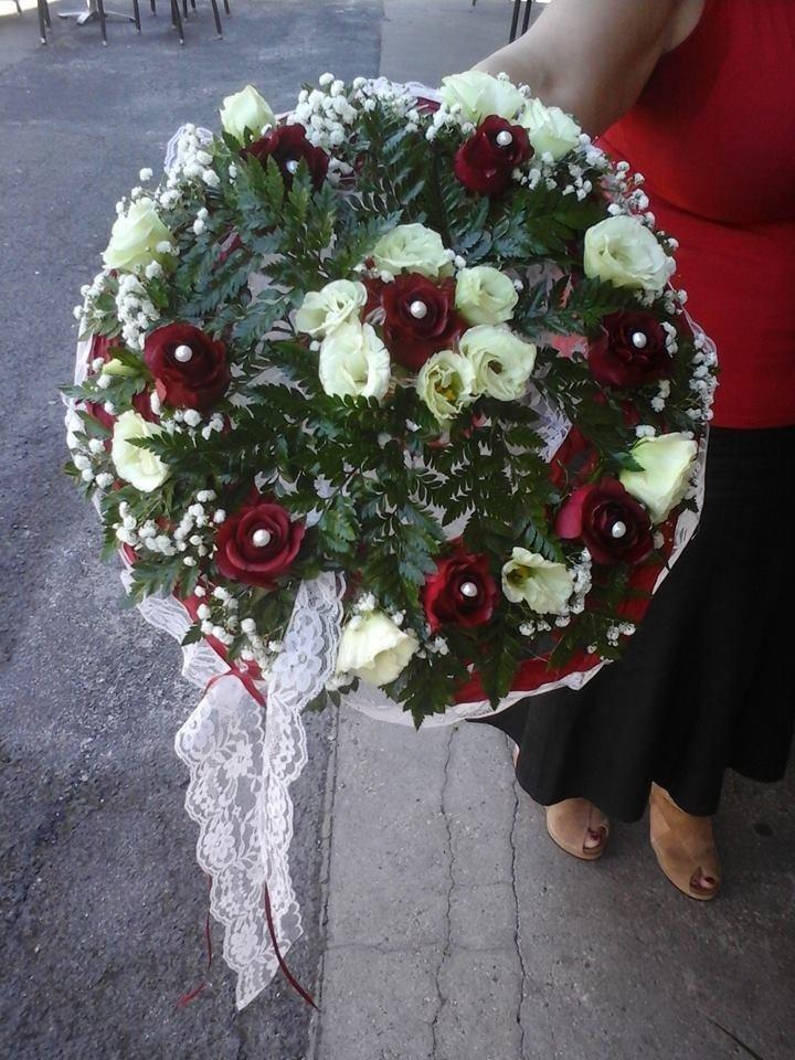 bouquet con rose bianche e rosso tiene una donna con mano