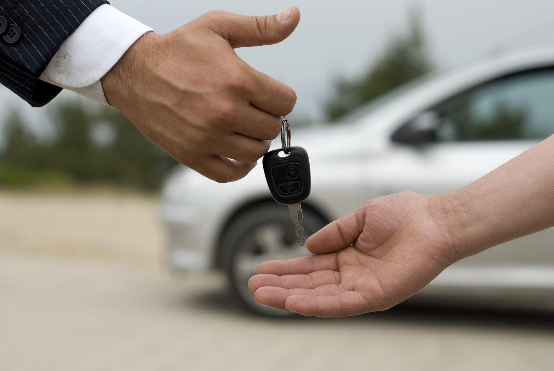 Una mano passa la chiave di un'auto a un'altra mano