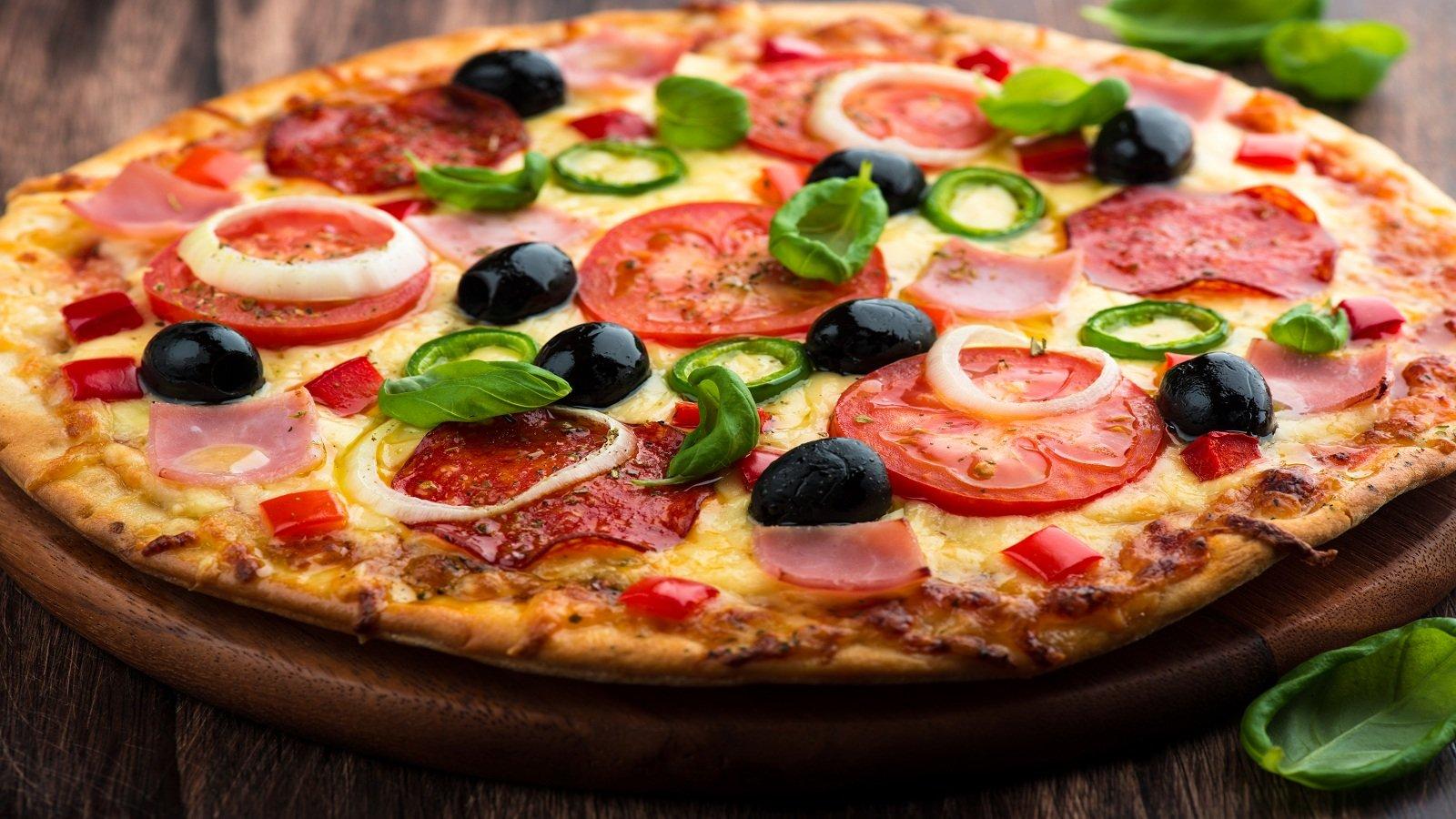 una pizza con salame, pomodori, olive nere,peperoni e cipolle