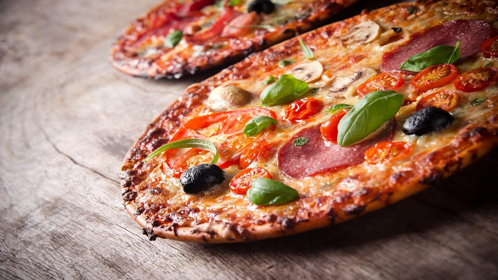 una pizza con salame, olive nere, mozzarella e pomodori