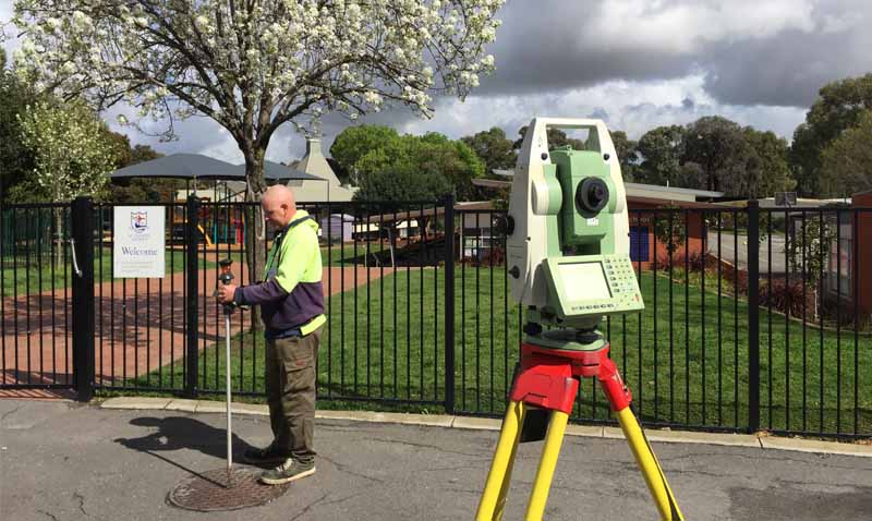 man carrying out a detail survey near school