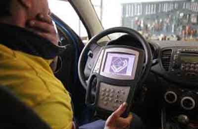 un meccanico in una macchina con un dispositivo di diagnostica attaccato al volante