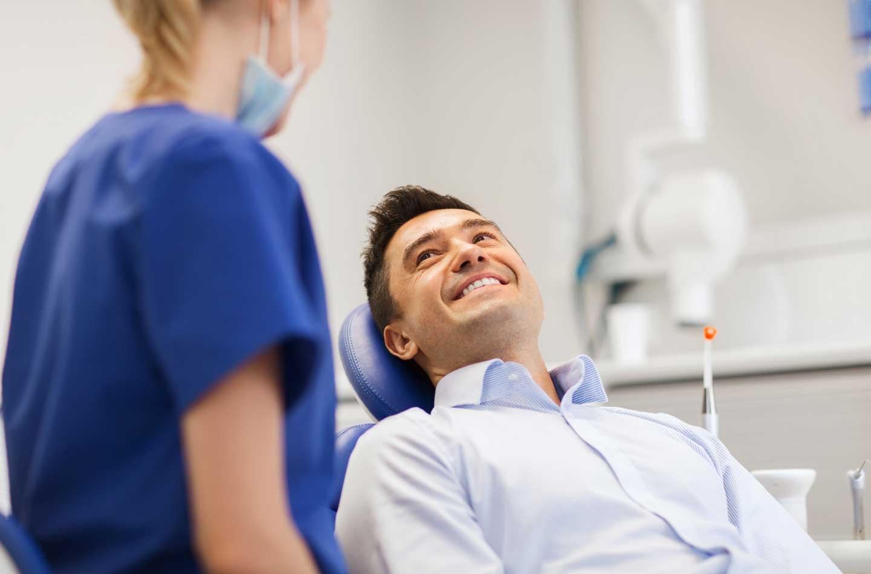 dentista mentre visita una paziente