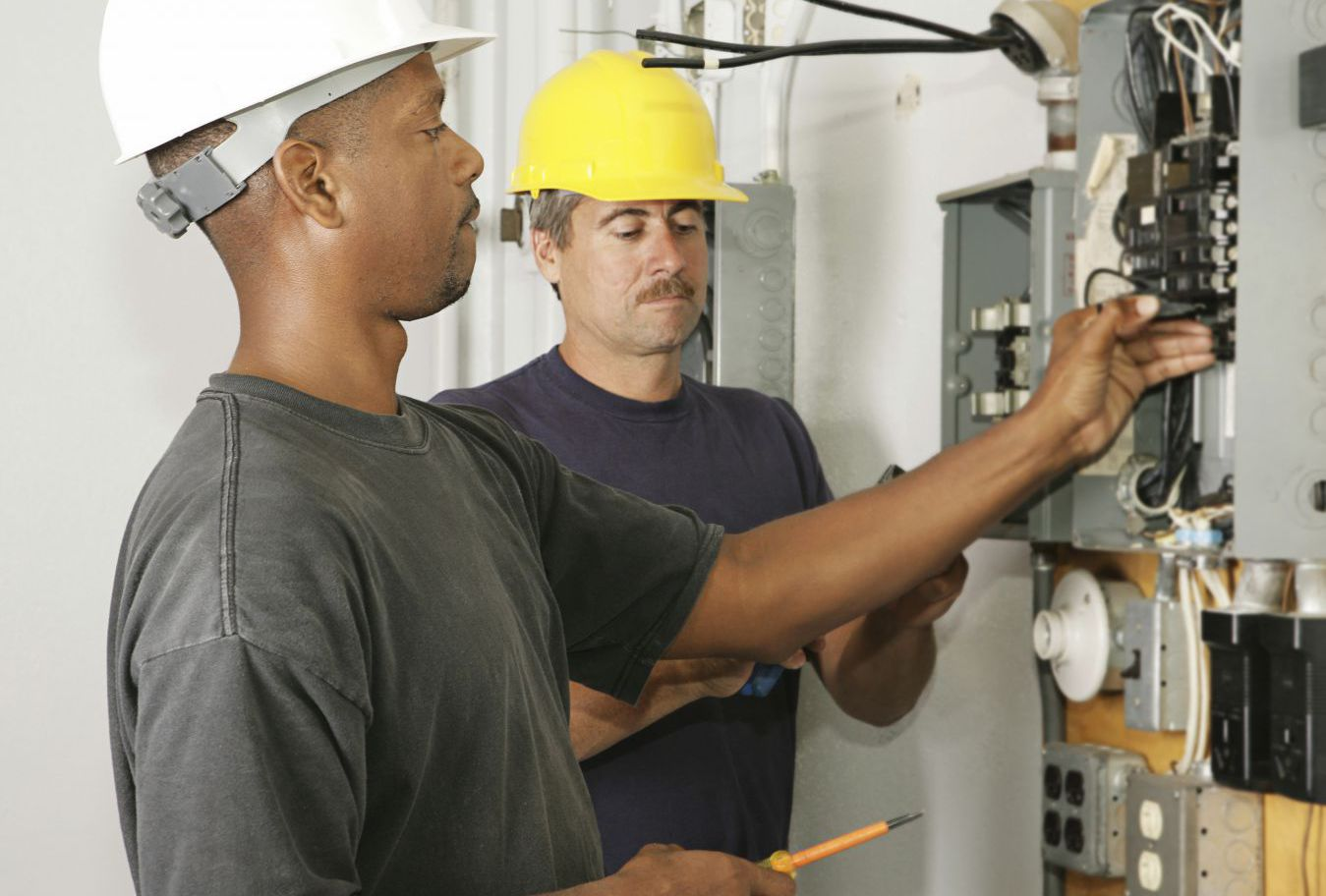 Electrician and assistant repairing fuse box in Augusta, WI