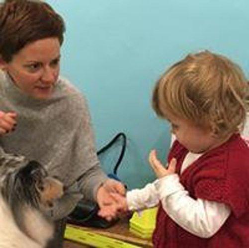 insegnante aiuta un bambino ad accarezzare un cane