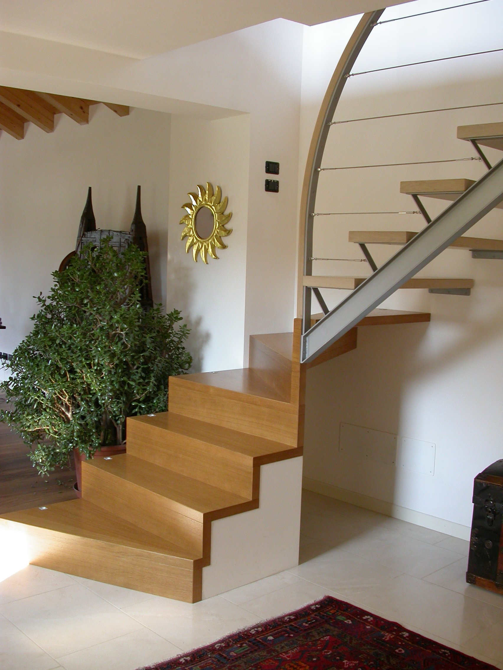 scala in legno in soggiorno e pianta