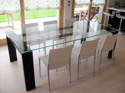 sala da pranzo con tavolo in cristallo e parquet