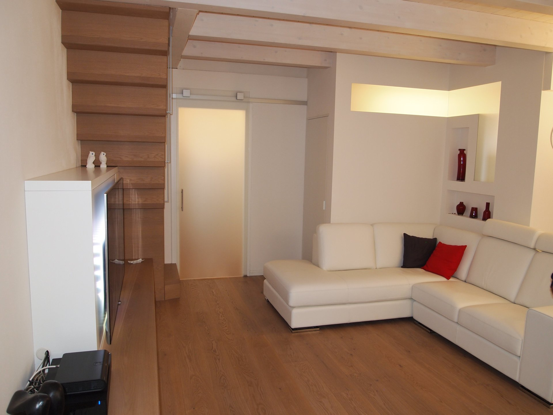 scala, pavimento in legno e divano con cuscini