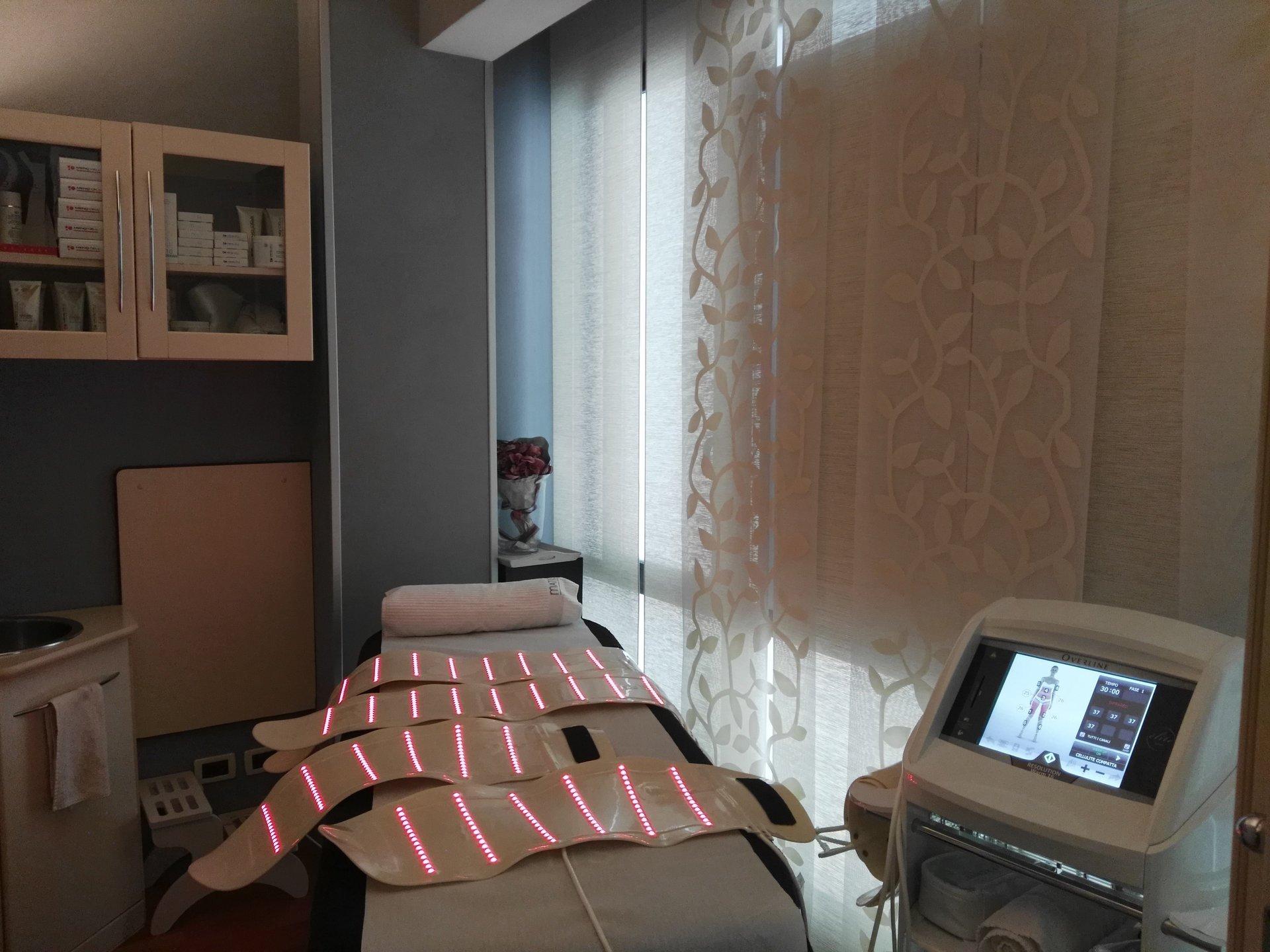 stanza di un centro estetico con lettino e strumenti laser