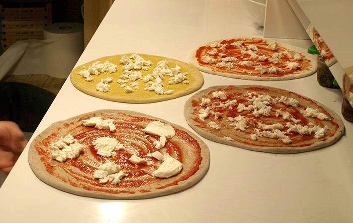 Pizze stese e condite con gusti vari
