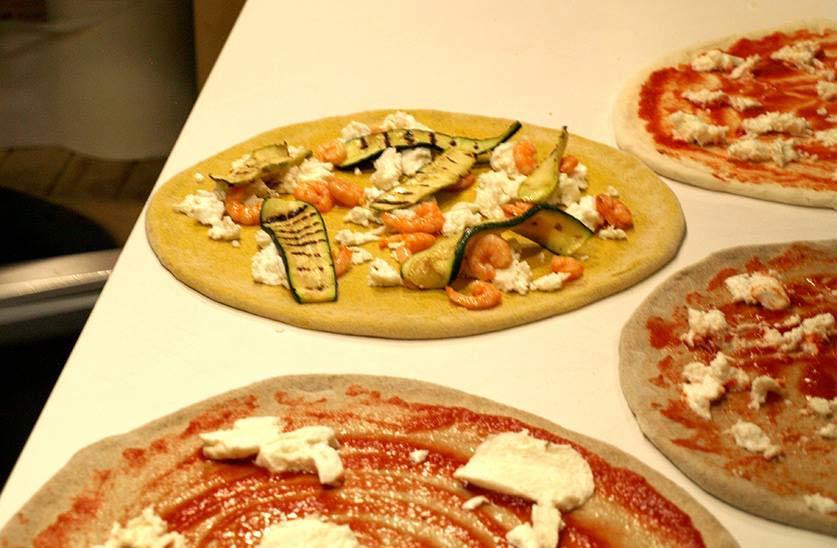 Pizze stese e condite pronte per essere infornate