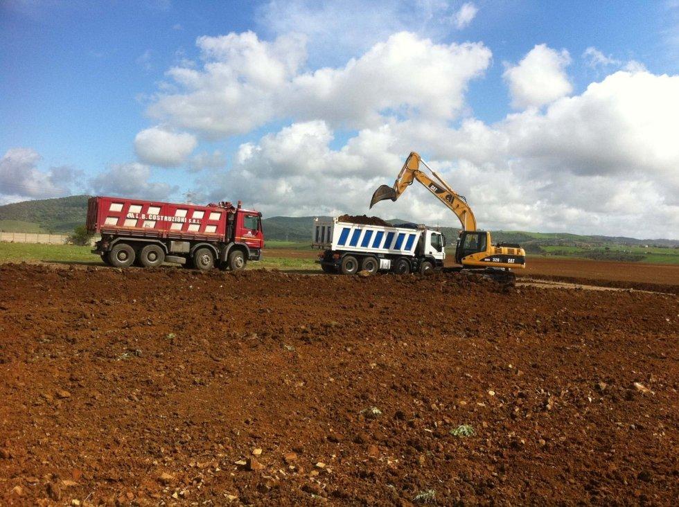 camion rosso e camion bianco con movimento terra in un campo