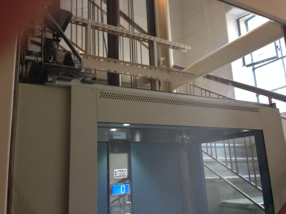 interno di un ascensore con sulla destra un display con la pulsantiera che segna il piano 0
