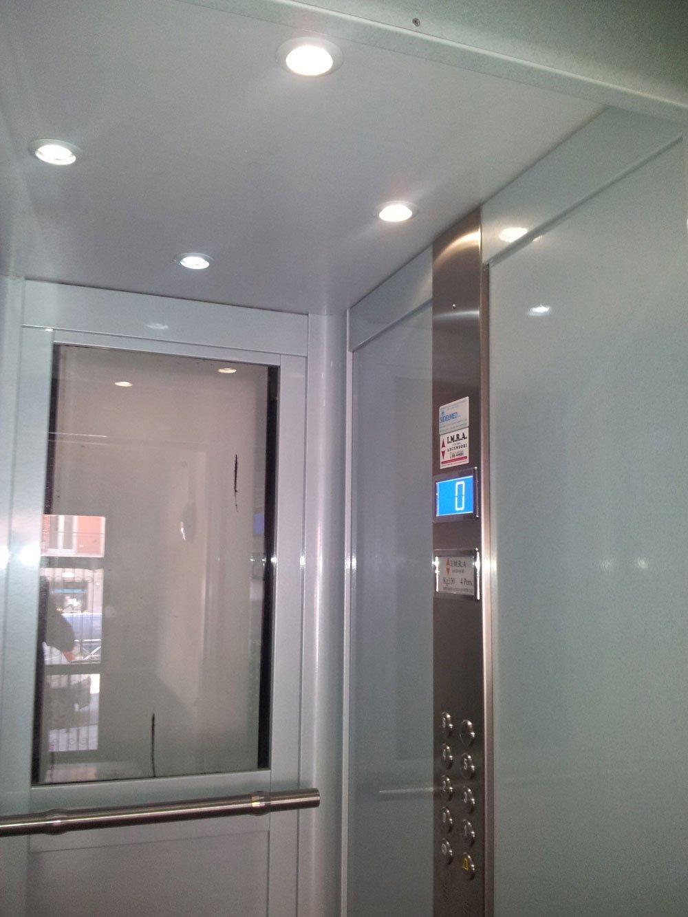 interno di un ascensore con uno specchio di fronte e sulla destra i tasti e uno schermo azzurro
