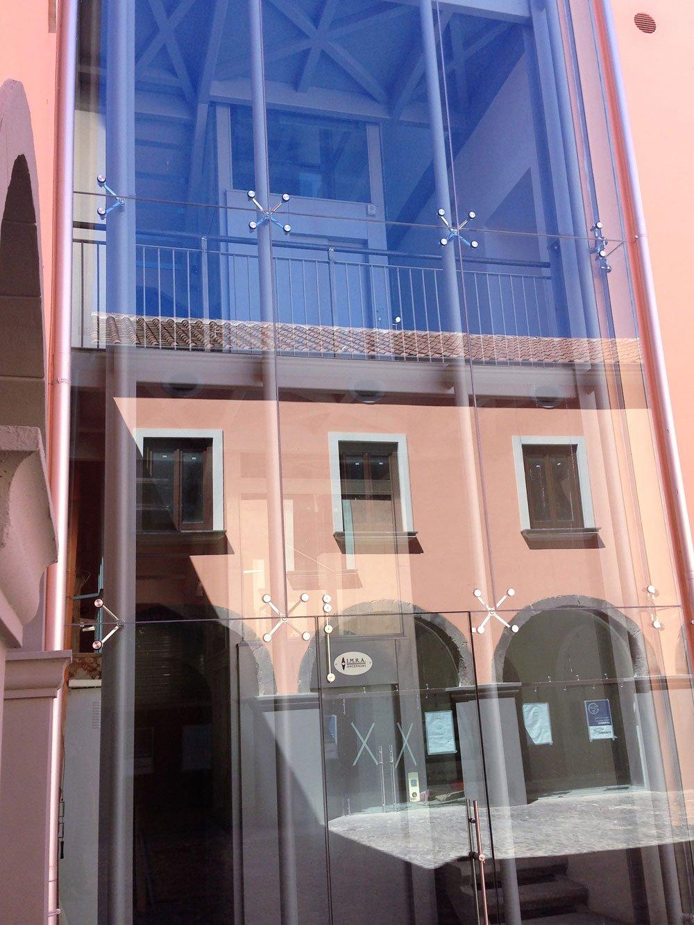 vista del vetro di un ascensore esterna e del riflesso di un condominio colo rosa
