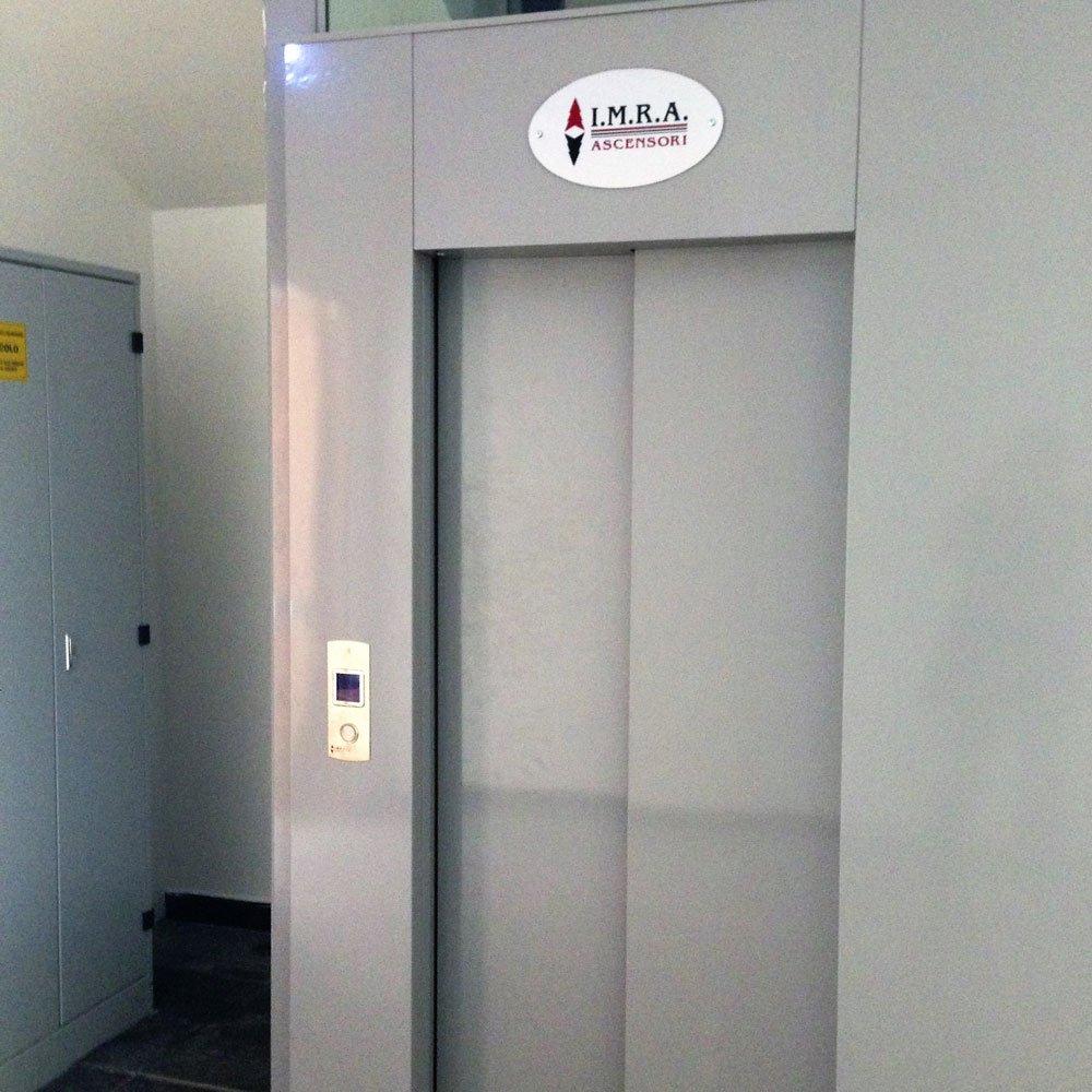 vista della porta di un ascensore color grigio con scritto IMRA
