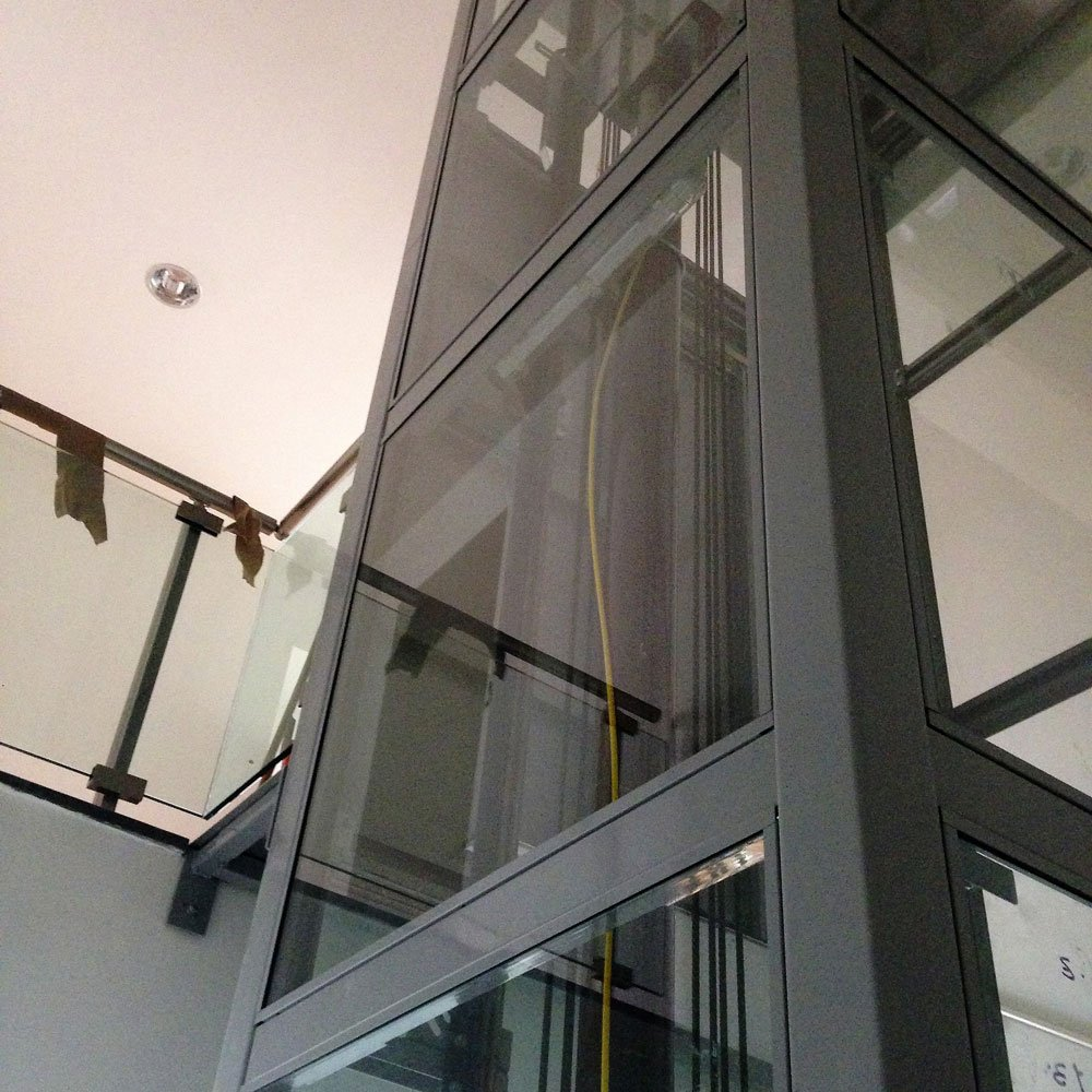 vista dal basso verso l'alto della struttura in ferro e vetro che ospita l'ascensore con all'interno un cavo giallo