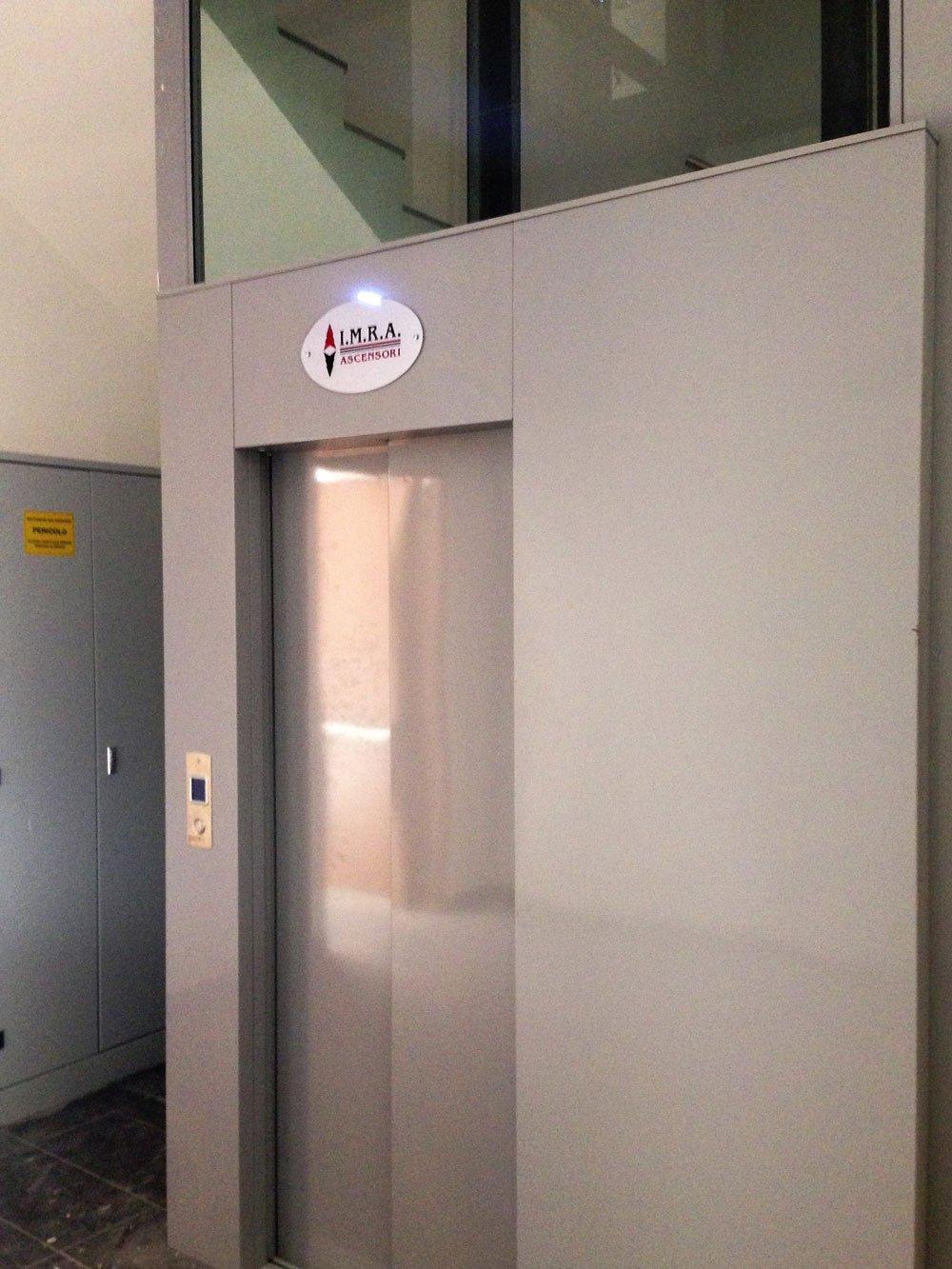 vista della porta di un ascensore un  metallo di color grigio con la scritta IMRA