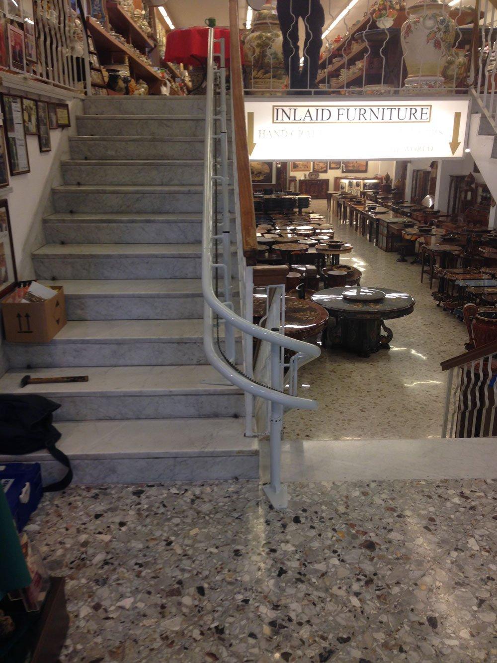 vista da un pianerottolo di una scala con sulla destra dei tavoli esposti con una scritta Inlaid Forniture