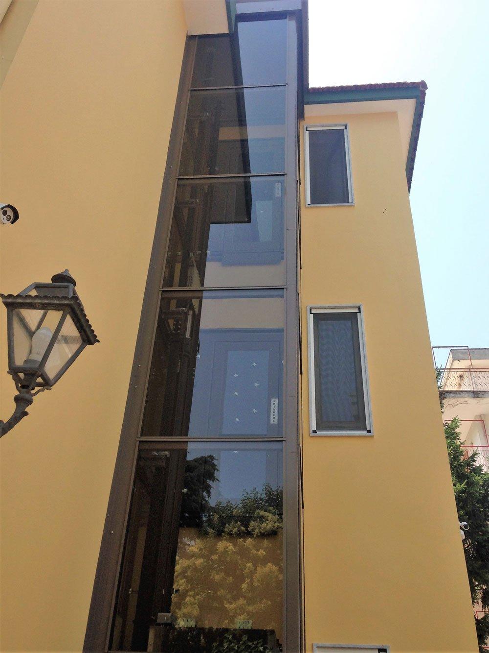 una struttura di ferro e vetro che ospita un ascensore esterna vicino a un condominio color sabbia