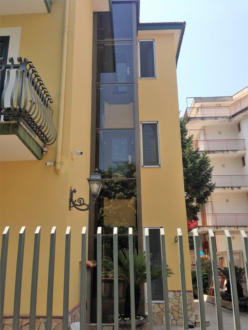 vista di una ringhiera in ferro e dietro un condominio color sabbia con un ascensore esterna