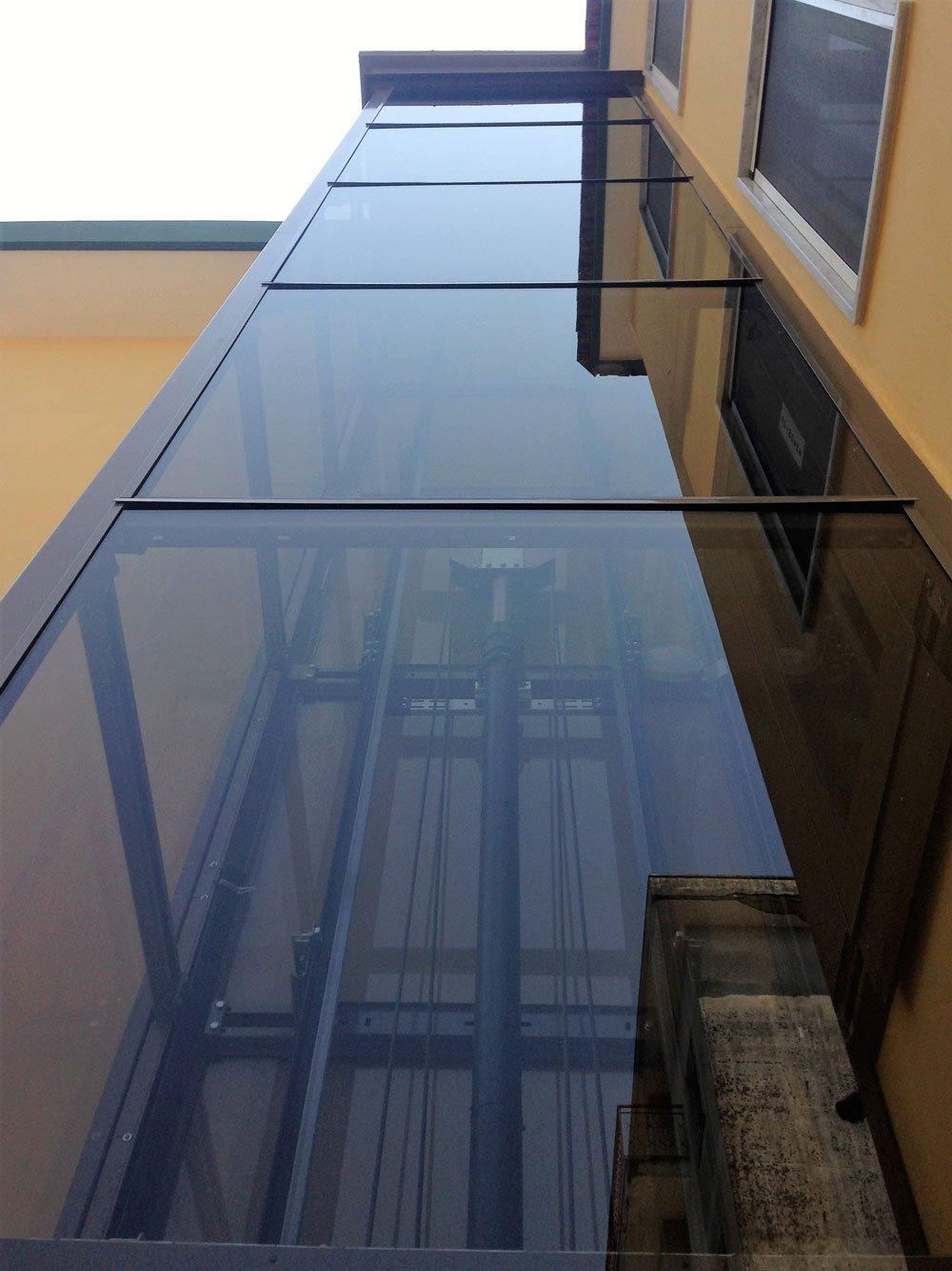vista dall'alto in basso della cabina in vetro che ospita l'ascensore all'esterno di uno stabile