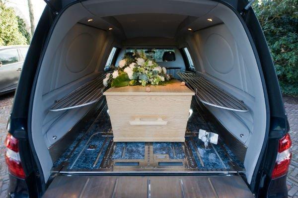 un carro funebre che contiene bara in legno