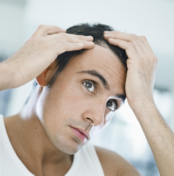 A man inspects his hair in the mirror