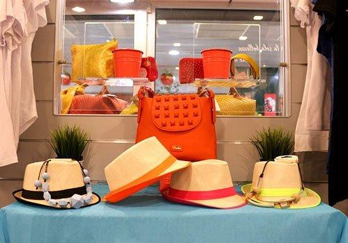 dei cappelli di paglia con dei nastri e una borsa arancione