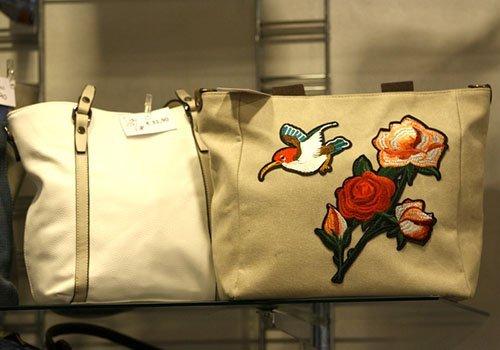 una borsa bianca e una beige con i disegni di un uccello e dei fiori arancioni