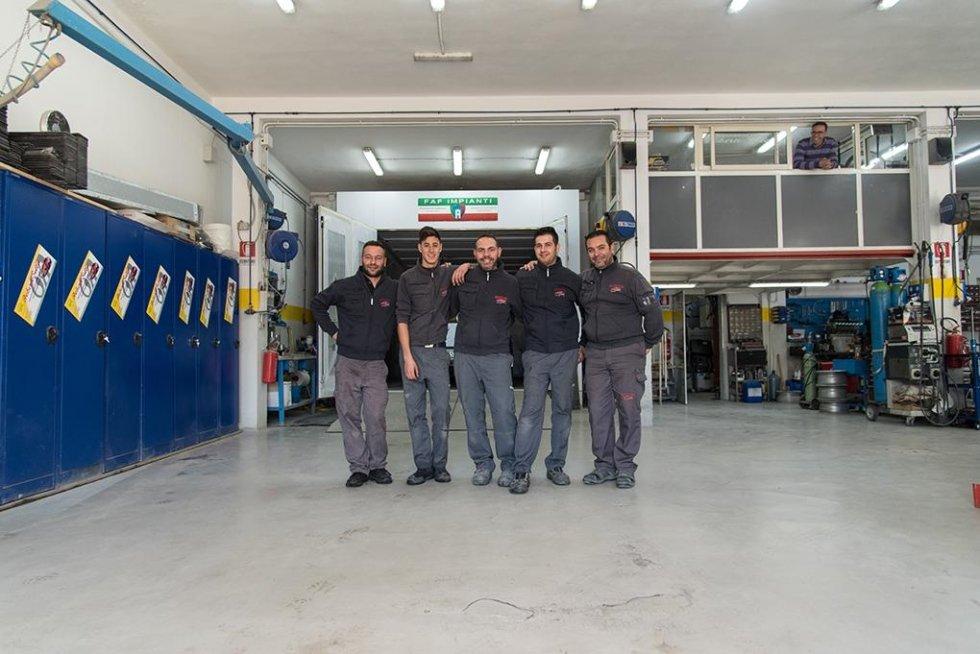un gruppo di meccanici in posa per una foto