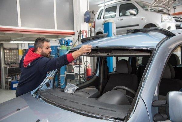 un meccanico vicino a una macchina con il vetro anteriore smontato
