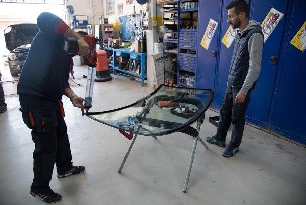 un meccanico con una lastra di un vetro anteriore di una macchina