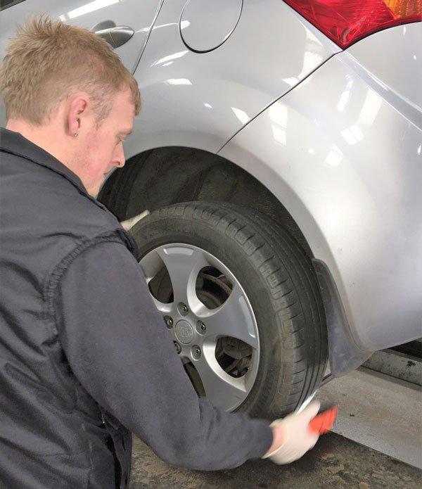 man inspecting wheel