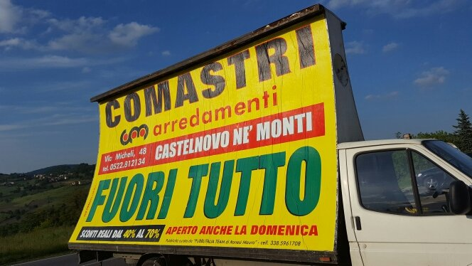 furgone con cartellone pubblicitario giallo