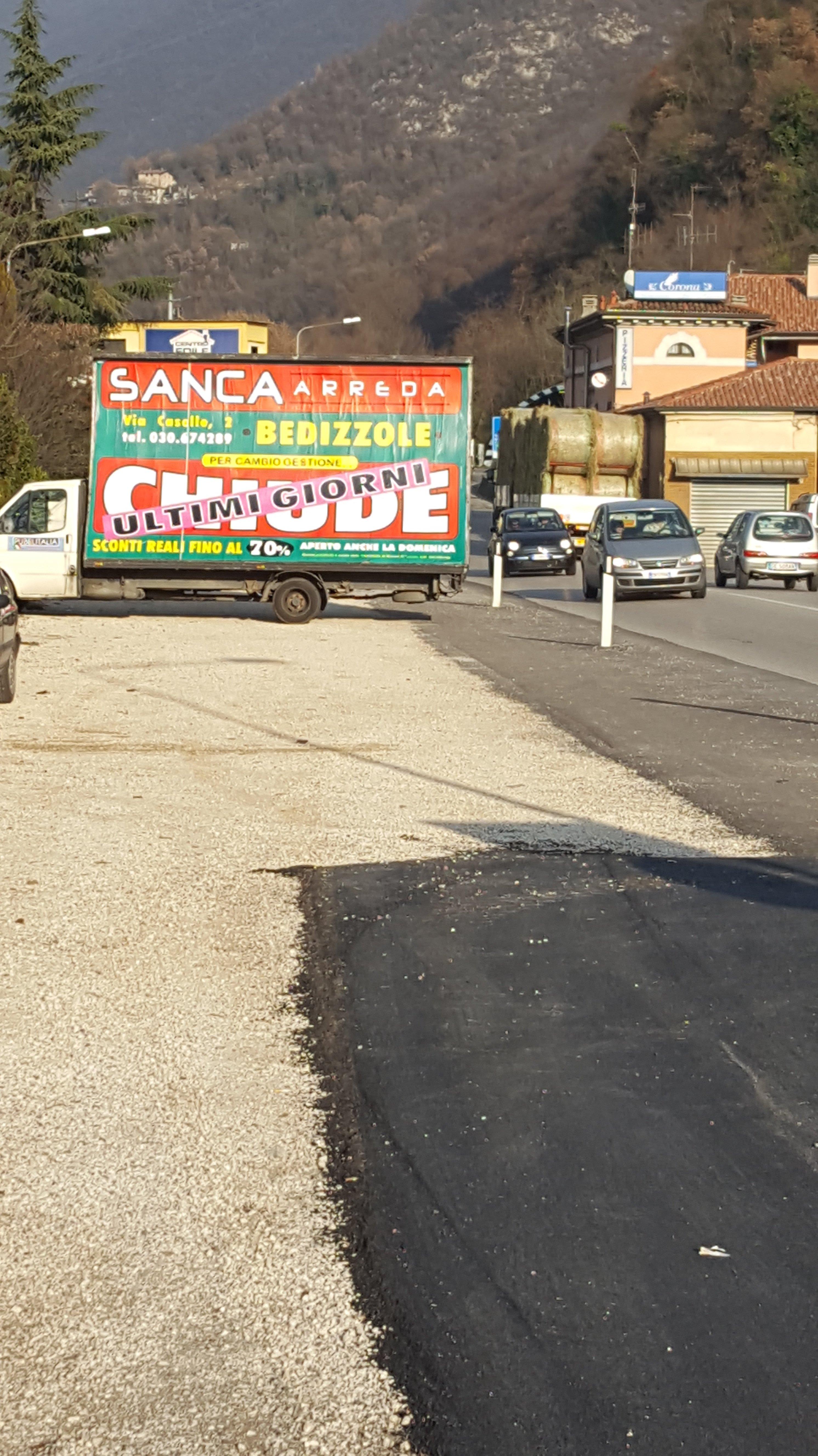 furgone con cartellone pubblicitario parcheggiato in strada